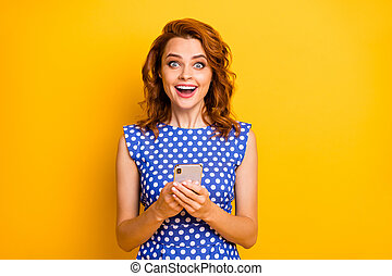 Portrait of her she nice attractive lovely amazed addicted cheerful cheery wavy-haired girl using cell positive news like isolated on bright vivid shine vibrant yellow color background
