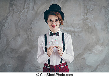 Portrait of her she nice attractive pretty lovely classy cheerful cheery wavy-haired girl dealing with paper cards blackjack isolated on gray concrete industrial wall background