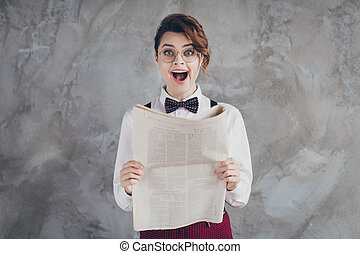 Portrait of her she nice-looking attractive lovely smart clever amazed cheerful wavy-haired girl reading periodic great news isolated on gray concrete industrial wall background