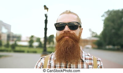 Portrait of hipster bearded tourist man in sunglasses looking at camera and smiling at city background