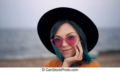 Portrait of hipster girl with unique fashionable blue hairstyle and hat on beach. Unusual woman in sunglasses with dyed colorful hair. High quality FullHD footage