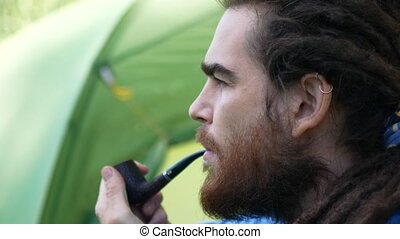 Portrait of hipster man with dreadlocks smoking cigarette. Side view