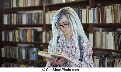 Portrait of hipster woman reading red book in library -...