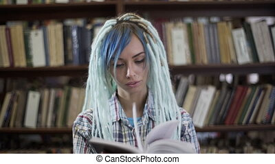 Portrait of hipster woman with dreadlocks reading book in...