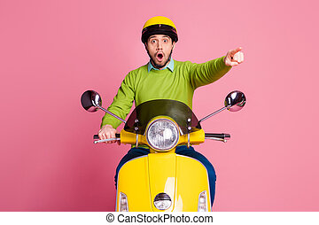 Portrait of his he nice attractive amazed worried guy sitting on moped pointing forefinger faraway look isolated over pink pastel color background