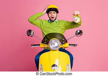 Portrait of his he nice attractive unlucky sad nervous worried guy riding moped holding in hand alarm clock isolated over pink pastel color background