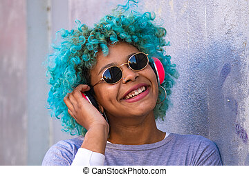 portrait of hispanic afro american woman with headphones and mobile phone smiling on the street