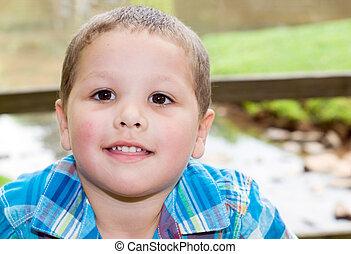 Portrait of Hispanic boy at park