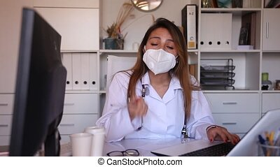 Portrait of hispanic female doctor wearing disposable face mask and white coat standing in medical office
