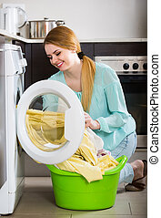 Portrait of housewife with bed linen near washer - Portrait ...