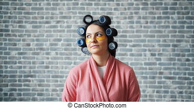Portrait of housewife with hair rollers and eye patches on...