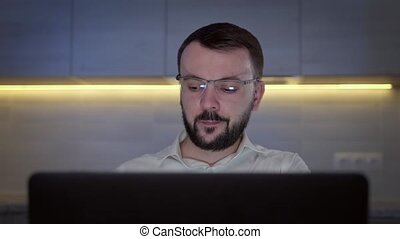 Portrait of hungry unshaven caucasian man with glasses eating fried french fries from fast food restaurant, watching video on laptop screen at home in dark room.
