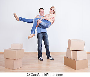 Portrait Of Husband Holding Wife In New Home
