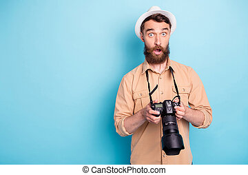 Portrait of impressed man holding his camera looking wearing brown shirt isolated over blue background