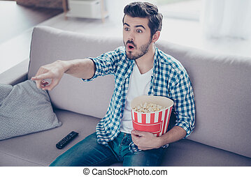 Portrait of impressed man in checkered shirt eating popcorn while watching films on tv at home and having fun