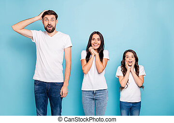 Portrait of impressed three brown hair people hear information scream wow omg wear white t-shirt denim jeans good look isolated over blue color background