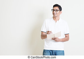 Indian guy taking note on book