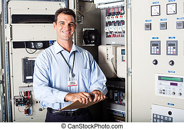 portrait of industrial engineer in front of computerized...