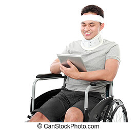 injured young man in wheelchair play on a tablet