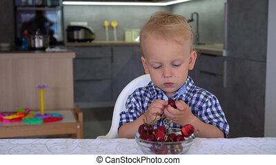 Portrait of innocent boy eating cherries at home by table....