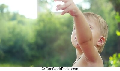 Portrait of interested little baby showing of hand to the sky nature outdoors in slow motion. 1920x1080