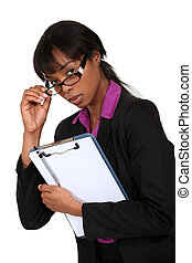 portrait of intimidating black businesswoman with glasses lowered holding clipboard