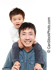 father giving his son piggy back - portrait of Japanese...