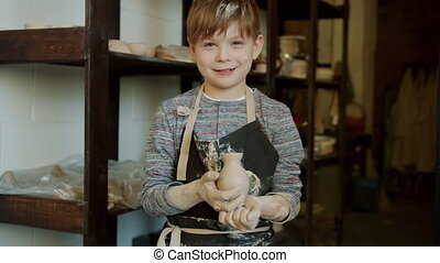 Portrait of joyful boy young potter holding hand-made vase in workshop standing alone smiling looking at camera. Child is wearing dirty apron.