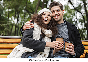 Portrait of joyful couple man and woman 20s drinking takeaway coffee from paper cups, while sitting on bench in green park