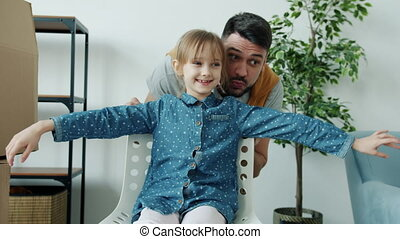 Portrait of joyful father having fun with cute child pushing her chair talking laughing