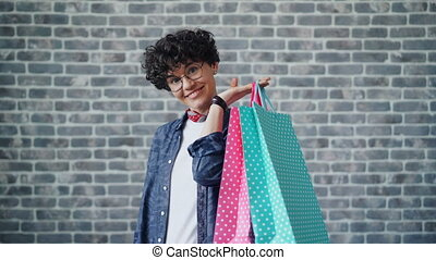 Portrait of joyful girl shopaholic holding shopping bags...