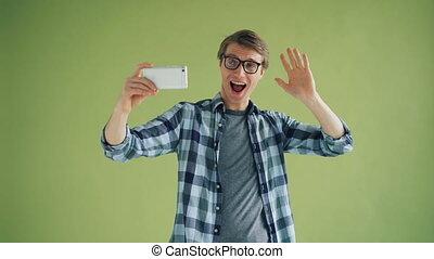 Portrait of joyful guy taking selfie with smartphone camera having fun