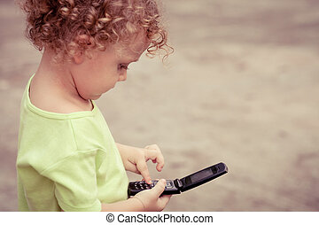 Portrait of joyful little boy holding a cellphone