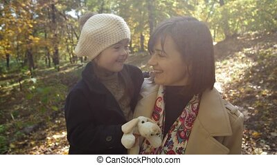 Portrait of joyful mom with special girl in arms
