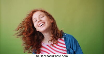 Portrait of joyful red-haired girl dancing and smiling on...