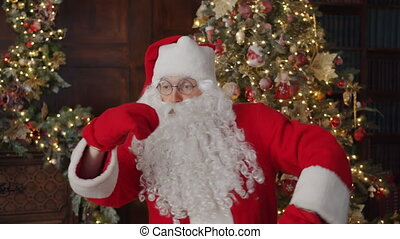 Portrait of joyful Santa dancing in decorated house moving arms in gloves having fun