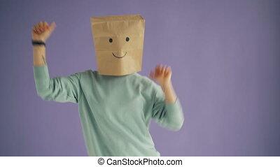 Portrait of joyful woman with paper bag on head dancing...