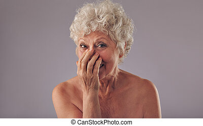 Portrait of joyous senor lady against grey background. Shirtless old woman smiling with hands on mouth.