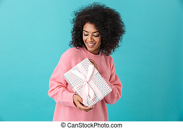 Portrait of joyous woman 20s with afro hairdo holding gift box and smiling in happiness, isolated over blue background