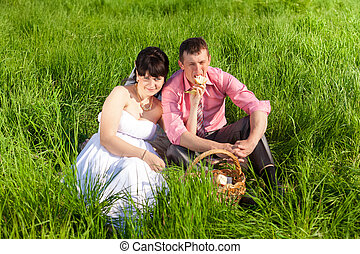 just bride feeding groom with banana on picnic