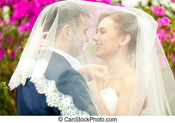 Portrait of just married couple under white veil
