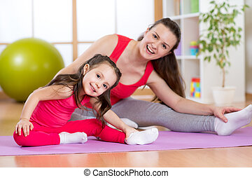 Portrait of kid and mother doing physical exercise at home -...