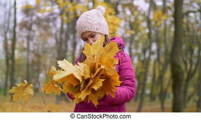 Portrait of kid holding bouquet of autumn foliage - Portrait...