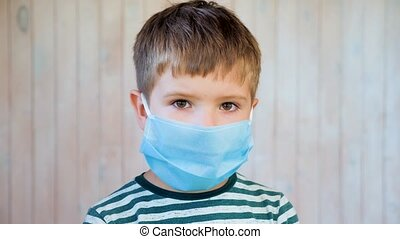 Portrait of kid wearing medical protective facemask in ...