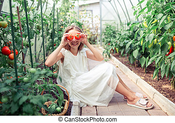 Portrait of kid with the big tomato in hands in greenhouse