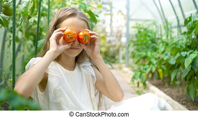 Portrait of kid with the big tomato in hands in greenhouse -...