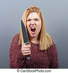 Portrait of killer woman with knife against gray background