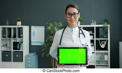 Portrait of lady medic in uniform holding green chroma key ...