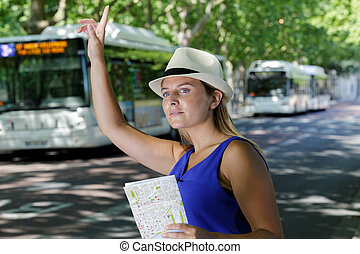 portrait of lady outdoors on street calling a taxi