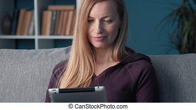 Portrait of lady sitting at apartment and using tablet